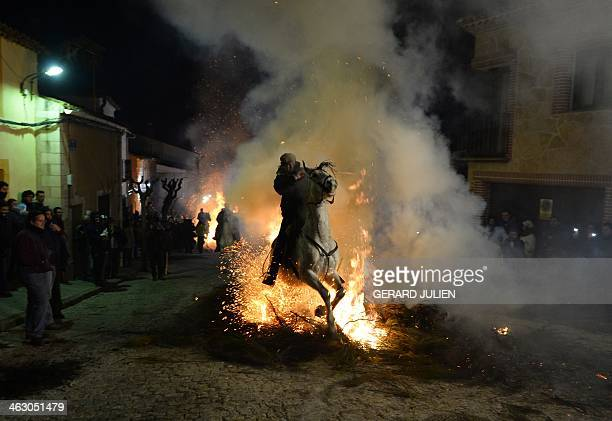 A horse and rider jump over a burning pyre in the central Spanish village of San Bartolome de Pinares on January 16 2014 during celebrations for the...