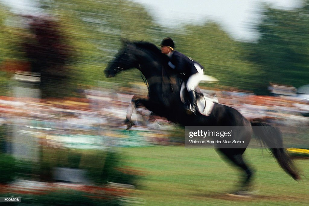 Horse and rider jumping fence
