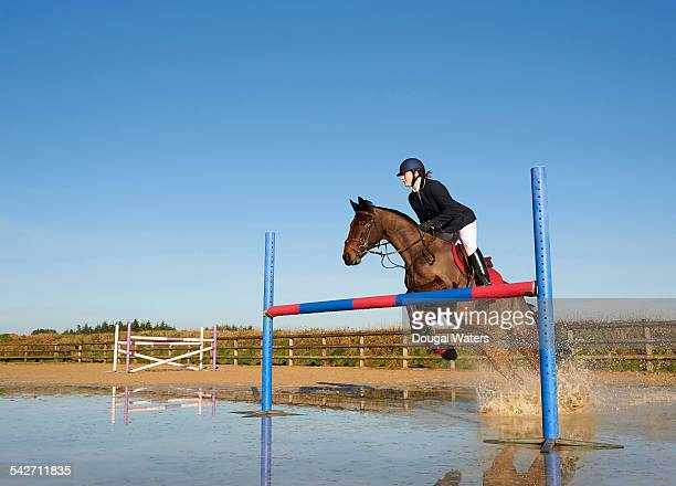Horse and rider jumping over fence.