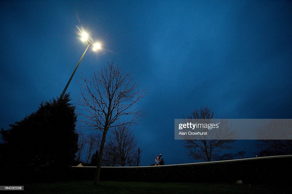 Horse and rider make their way to the course at Kempton racecourse on March 21, 2013 in Sunbury, England.