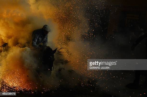 A horse and rider pass through a burning pyre in the central Spanish village of San Bartolome de Pinares on January 16 2014 during celebrations for...