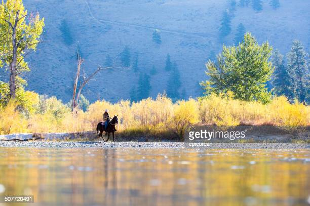 Horse and rider walk along western river bank