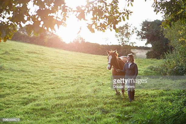 Horse and rider walking in countryside.