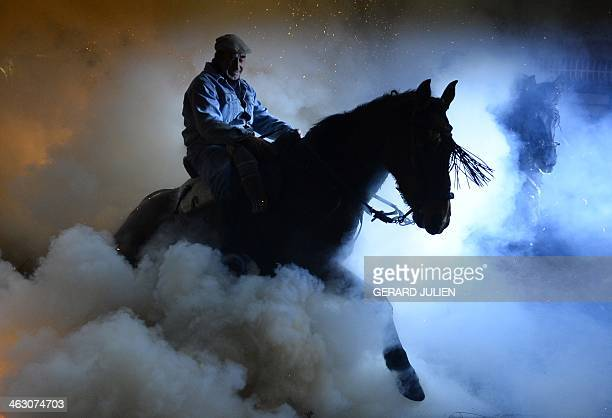 A horse and rider walks over a burning pyre in the central Spanish village of San Bartolome de Pinares on January 16 2014 during celebrations for the...