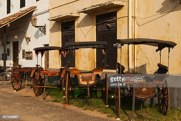 Horse carts parked alongside building