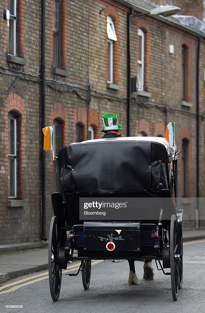 A horse drawn carriage, decorated with Irish national flags is seen traveling through Dublin, Ireland, on Saturday, March 16, 2013. Ireland's renewed competiveness makes it a beacon for the U.S. companies such as EBay, Google Inc. and Facebook Inc., which have expanded their operations in the country over the past two years. Photographer: Simon Dawson/Bloomberg via Getty Images