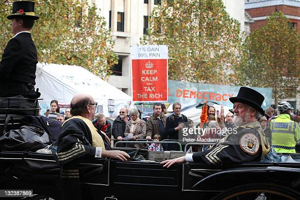 A horse drawn carriage passes Occupy London protestors outside St Paul's Cathedral during the Lord Mayor's Show on November 12 2011 in London England...