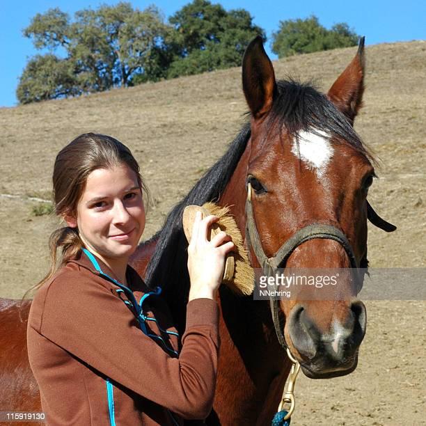 horse grooming by teenage female