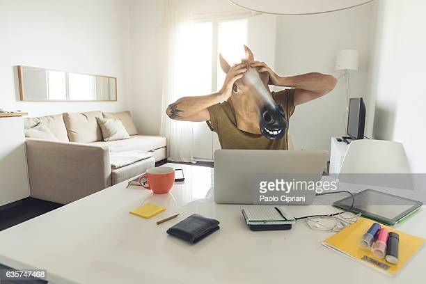 Horse head man working on laptop at home