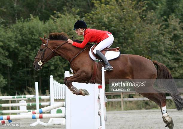 Horse jumping competition show with rider in red
