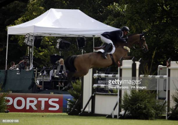 A horse jumps in front of the Sky Sports presenting podium in the Furusiyya FEI Nations Cup of Great Britain presented by Longines during day four of...