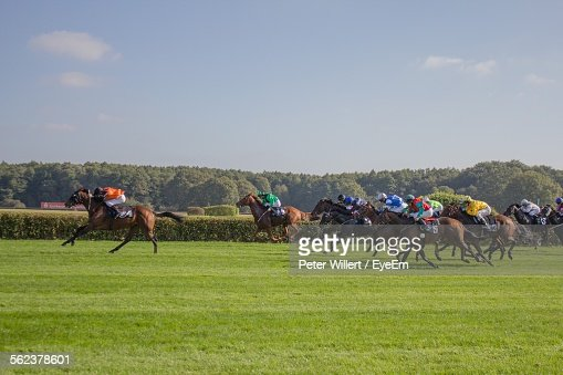 Horse Race On Grassy Field Against Sky