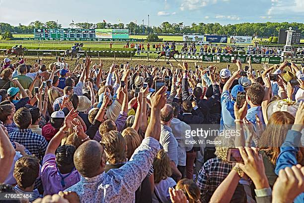 Belmont Stakes Overall view of fans victorious watching Victor Espinoza in action aboard American Pharoah cross finish line with their camera phones...