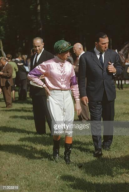 A horse racing jockey walks alongside a burly man in a dark grey suit possibly in Europe June 1960
