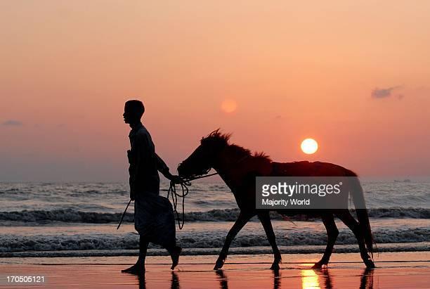 A horse renter walks along the Parkichar sea beach at sun set Chittagong Bangladesh May 11 2007
