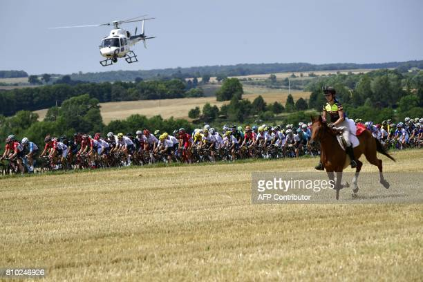 TOPSHOT A horse rider is pictured in front of the pack riding as a media helicopter flies over the pack during the 2135 km seventh stage of the 104th...