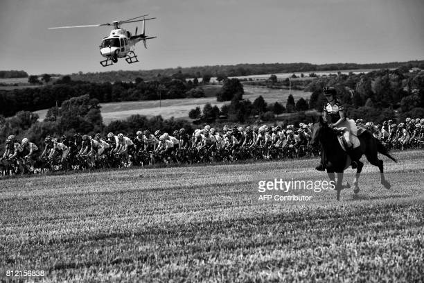 A horse rider is pictured in front of the pack riding as a media helicopter flies over the pack during the 2135 km seventh stage of the 104th edition...