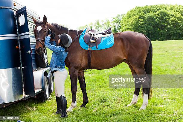 Horse rider putting on horse's bridle
