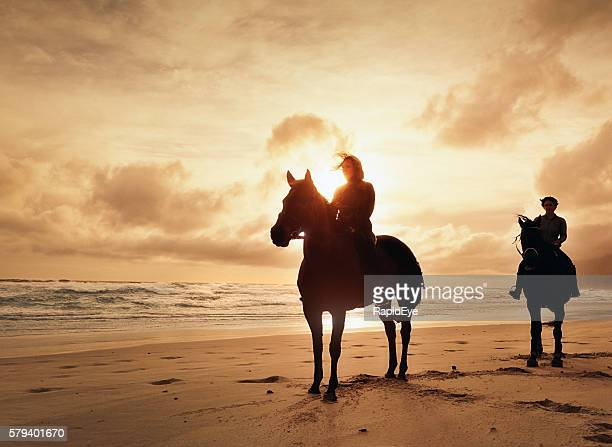 Horse riders silhouetted against setting sun on winter beach