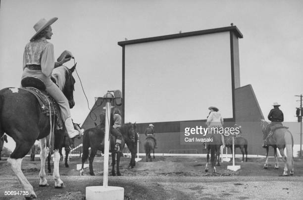 Horseback riders in cowboy garb taking positions at speaker posts while settling in to watch the evening's feature at a DriveIn movie theater