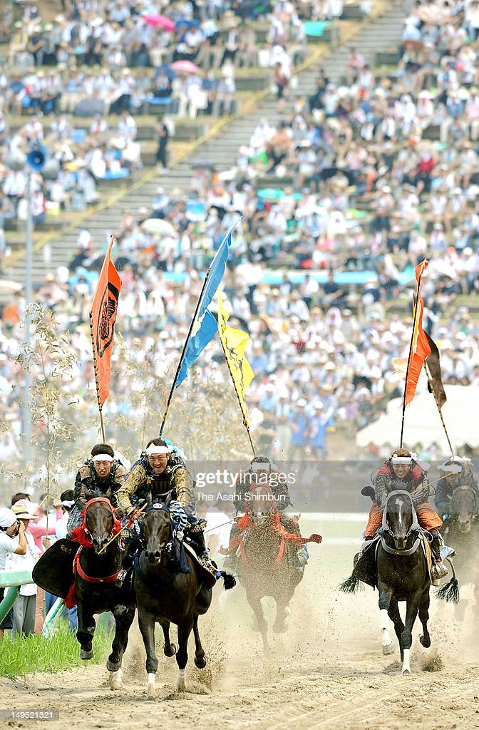 Horseback riders in full-body armor compete during the 'Soma Nomaoi Festival' on July 23, 2012 in Minamisoma, Fukushima, Japan. Some 400 riders participate in this year's festival though most of them are still evacuated after the Fukushima Daiichi Nuclear Power Plant accident.
