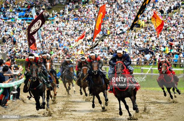 Horseback riders in fullbody armor compete in the 'Kacchu keiba' horse racing during the 'Soma Nomaoi Festival' on July 30 2017 in Minamisoma...