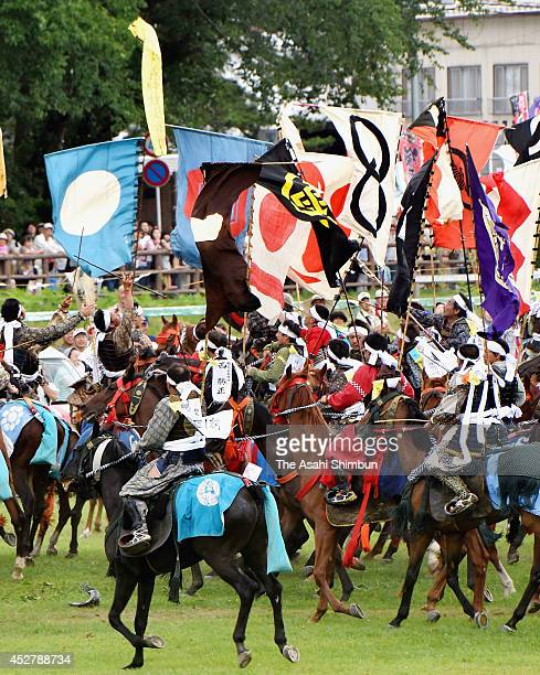 Horseback riders in fullbody armor compete in the 'Shinki Sodatsusen' pursuit of the Goshinki 'sacred flag' during the 'Soma Nomaoi Festival' on July...