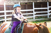 Little girl holding on to the saddle during riding lesson.