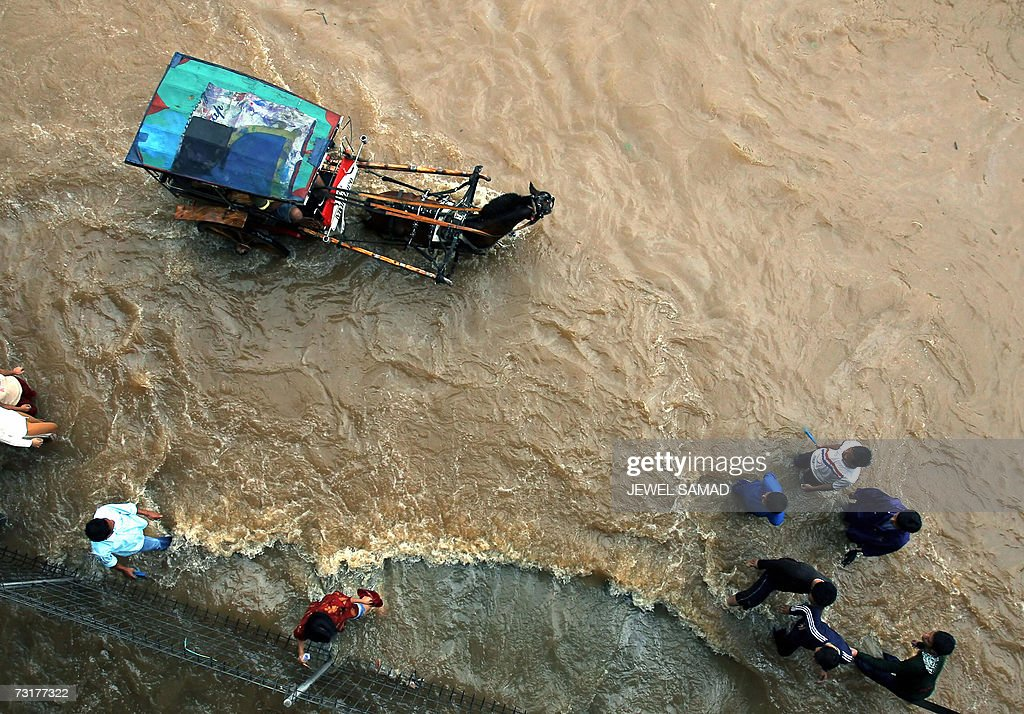 A horse-cart is driven past residents along a flooded street in downtown Jakarta, 02 February 2007. Floods blocked roads and railways in Jakarta and thousands of people abandoned their homes in low-lying areas as torrential downpours virtually paralysed the Indonesian capital. AFP PHOTO/Jewel SAMAD