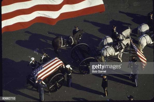 Horsedrawn caisson bearing flagdraped casket of John F Kennedy leads funeral cortege and is followed by riderless horse Washington DC
