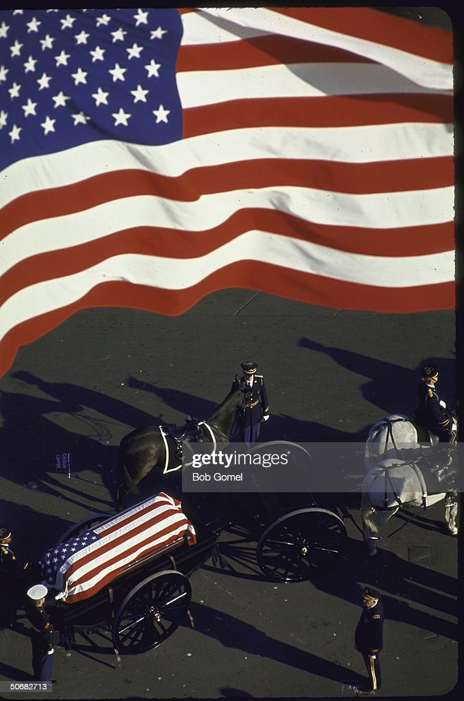 Horse-drawn caisson bearing flag-draped casket of John F, Kennedy leads funeral cortege and is followed by riderless horse, Washington, D.C.