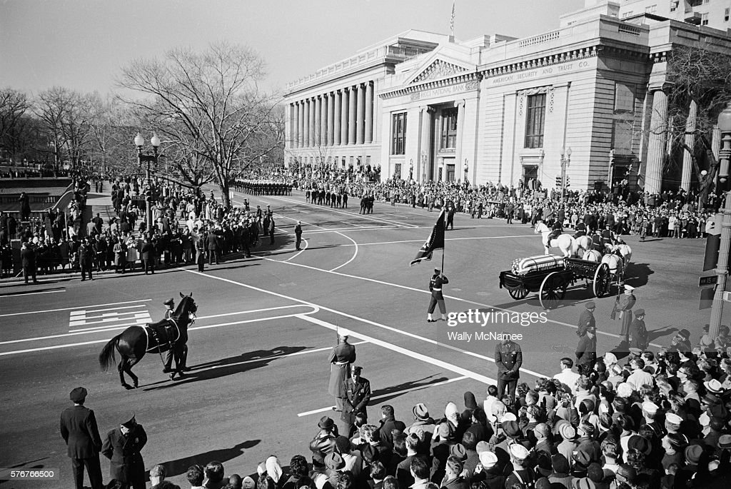 A horsedrawn caisson carrying the body of John Fitzgerald Kennedy passes mourners lining the streets of Washington DC