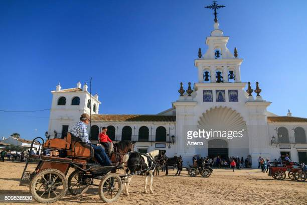 Horsedrawn carriage and pilgrims in front of the white Hermitage of El RocÕo / Ermita del RocÕo Almonte Province of Huelva Andalucia Spain