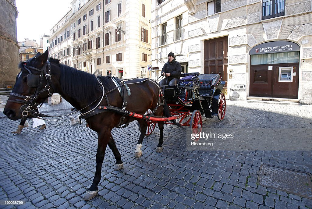 A horse-drawn carriage passes a Banca Monte dei Paschi di Siena SpA bank branch in Rome, Italy, on Friday, Jan. 25, 2013. Italian Prime Minister Mario Monti said the Bank of Italy will take another look at Banca Monte dei Paschi di Siena SpA's books after the company disclosed this week it may face more than 700 million euros of losses related to structured finance transactions hidden from regulators. Photographer: Alessia Pierdomenico/Bloomberg via Getty Images