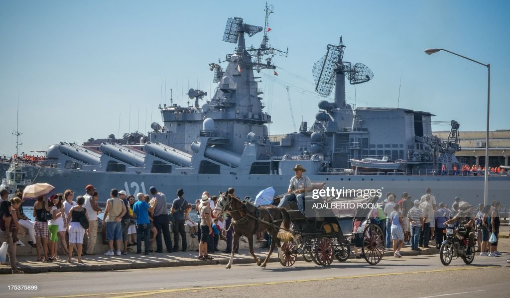 A horse-drawn carriage passes by as Cubans watcht the 'Moskva' Russian guide missile cruiser arriving at Havana's harbour, on August 3, 2013. The vessel is part of a three-ship group in official visit to Cuba. AFP PHOTO/Adalberto ROQUE