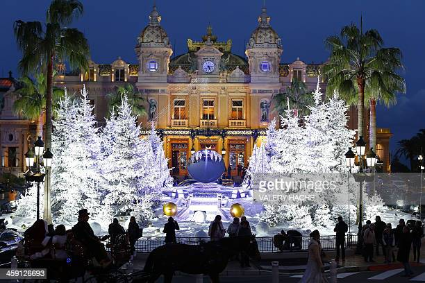 A horsedrawn carriage passes in front of the Monte Carlo Casino in Monaco decorated with Christmas lights and trees on December 23 2013 AFP PHOTO /...