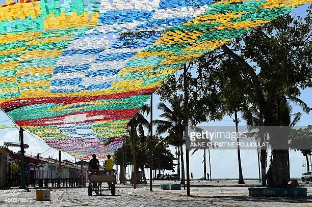 A horsedrawn carriage travels along a street under a canopy of national flags of countries participating in the forthcoming 2014 FIFA World Cup in...