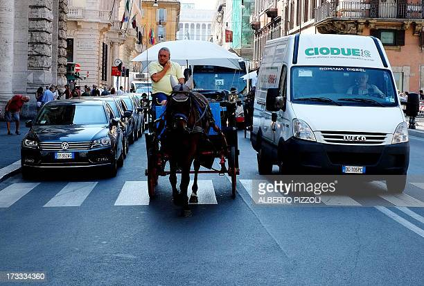 A horsedrawn carriage used for riding tourists in the citty rides Via del Corso on July 12 2013 in Rome In order to protect the animals Rome's city...