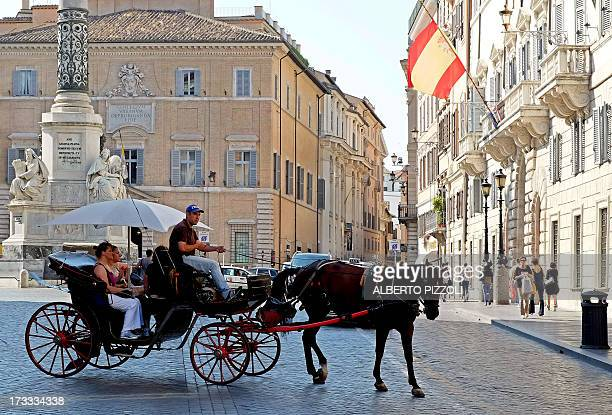 A horsedrawn carriage used for riding tourists in the city passes by piazza di Spagna on July 12 2013 in Rome In order to protect the animals Rome's...