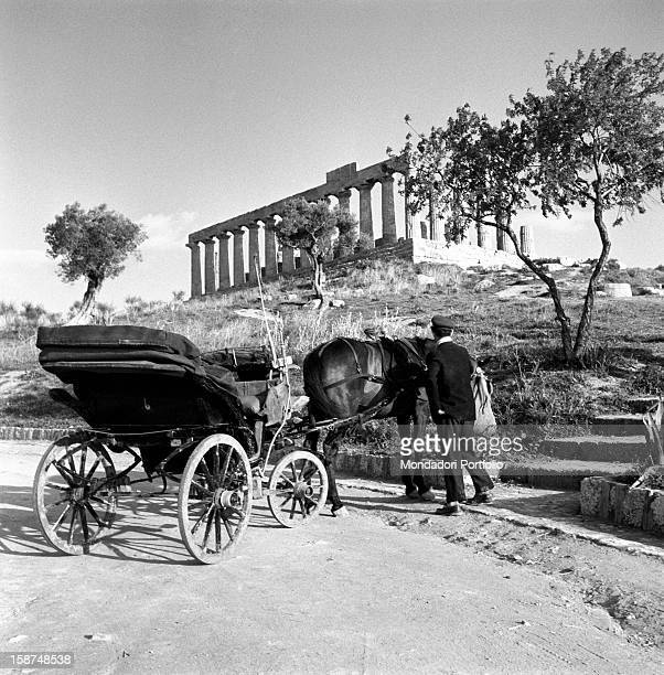 A horsedrawn carriage waiting at the foot of the Greek Temple of Concordia Agrigento 1955