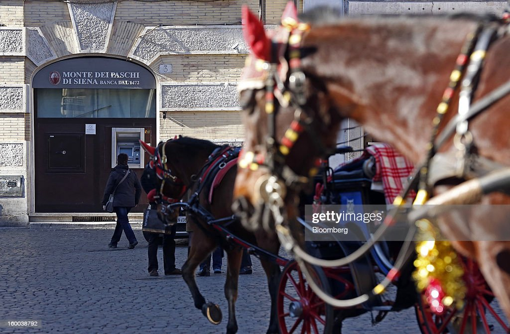 Horse-drawn carriages wait for customers near a Banca Monte dei Paschi di Siena SpA bank branch, left, in Rome, Italy, on Friday, Jan. 25, 2013. Italian Prime Minister Mario Monti said the Bank of Italy will take another look at Banca Monte dei Paschi di Siena SpA's books after the company disclosed this week it may face more than 700 million euros of losses related to structured finance transactions hidden from regulators. Photographer: Alessia Pierdomenico/Bloomberg via Getty Images