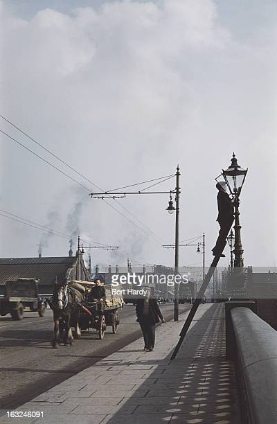 A horsedrawn cart crossing a bridge in Belfast Northern Ireland June 1955 A workman on a ladder is attending to a gas lamp Original publication...