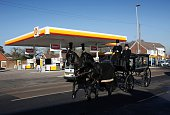 A horsedrawn funeral carriage passes a Royal Dutch Shell petrol station in Hook near Basingstoke on January 20 2016 Royal Dutch Shell said it...