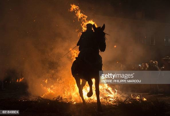 TOPSHOT A horseman jumps over a bonfire in the village of San Bartolome de Pinares in the province of Avila Castile and Leon in central Spain during...