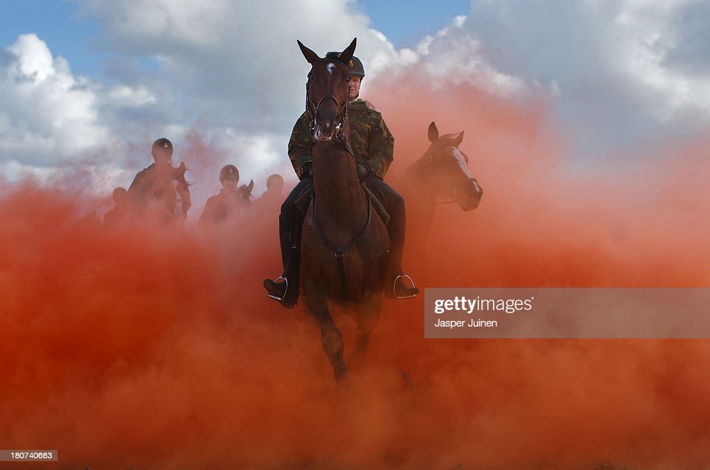 A horseman rides his horses through colored smoke during a practice session at the beach of Scheveningen on September 16, 2013 in Scheveningen, Netherlands. Some eighty members of the Dutch cavalry practiced for any possible emergency during tomorrow's Prinsjesdag ceremony which marks the opening of the Dutch parliament.
