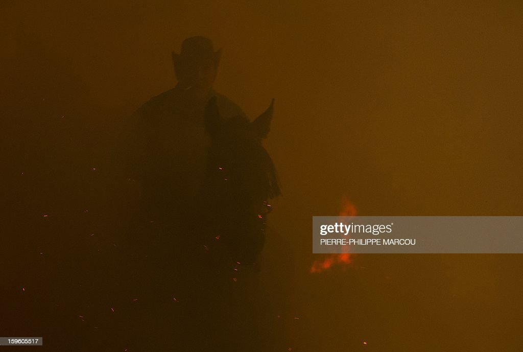 A horseman rides next to a bonfire in the central Spanish village of San Bartolome de Pinares during the celebrations for the feast of Saint Anthony, patron saint of animals, on January 16, 2013. AFP PHOTO/ PIERRE-PHILIPPE MARCOU