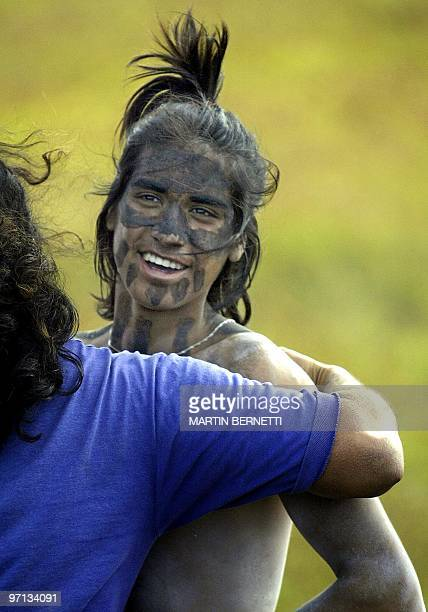A horseman whose face is painted with a substance called 'tacona' in the style of old Polynesian Matamua warriors is congratulated after winning a...