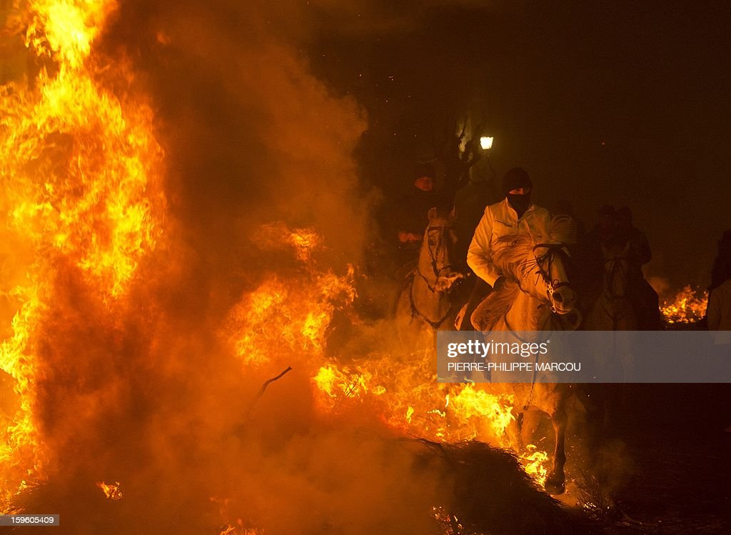 Horsemen jump over a bonfire in the central Spanish village of San Bartolome de Pinares to open the celebrations for the feast of Saint Anthony, patron saint of animals, on January 16, 2013. AFP PHOTO/ PIERRE-PHILIPPE MARCOU