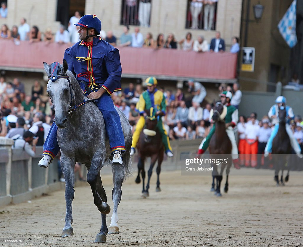 Horsemen ride in the main rehearsal at the Piazza del Campo on August 15, 2013 in Siena.The Palio races in Siena, in which riders representing city districts compete, and takes place twice a year in the summer in a tradition that dates back to 1656.