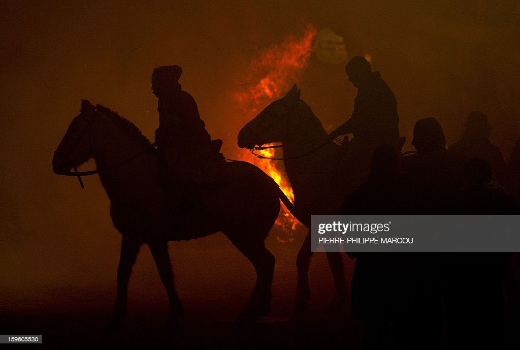 Horsemen ride next to a bonfire in the central Spanish village of San Bartolome de Pinares during the celebrations for the feast of Saint Anthony, patron saint of animals, on January 16, 2013. AFP PHOTO/ PIERRE-PHILIPPE MARCOU